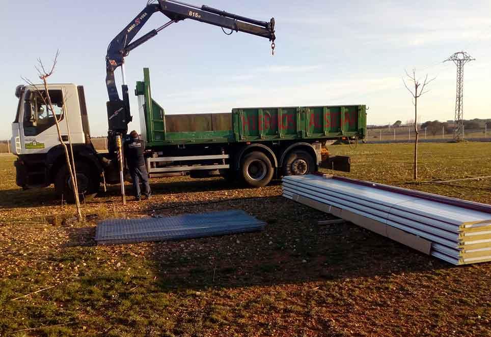 Lkw auf Wiese entlädt Baumaterial mit Kran